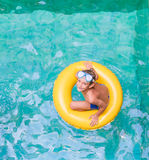 Swimming, summer vacation - child boy playing in blue wat Royalty Free Stock Images