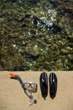 Swimming or surfing shoes and diving mask on beach Royalty Free Stock Photography