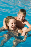 Swimming together. Mother and her son in the swimming pool royalty free stock photo