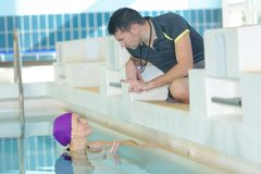 Swimming trainer giving advice to athlete. Swimming trainer giving advice to the athlete Royalty Free Stock Photo