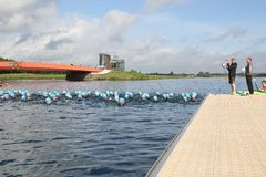 Swimming triathlon exercise healthy. Swimmers line up near the starting official for the swim leg of a triathlon at Dorney Lake near Windsor, England, on a Stock Images