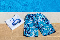 Swimming trunks goggles and towel at pool Stock Photography
