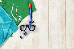 Swimming Trunks, Towel And Snorkeling Mask On Floorboard. Directly above shot of swimming trunks; towel and snorkeling mask on floorboard Royalty Free Stock Photos