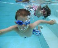 Swimming underwater. Boy and girl swimming underwater Royalty Free Stock Photo