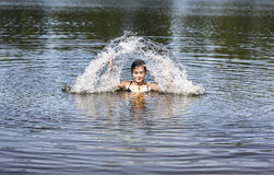 Swimming woman makes a water fountain. In summer Royalty Free Stock Photos