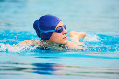 Swimming woman in pool. Fast swimming girl in blue water Stock Photo