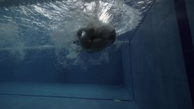 Swimming woman turning underwater and repelling by wall pool slow motion. Woman floating crawl stroke in transparent water swimming pool under water view 60 stock video