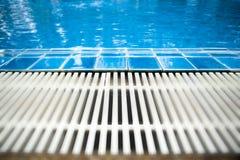 Swimmingpool, den das Bild vom Rand des Swimmingpools nahm, die von den blauen Fliesen und von der Gossenentwässerung zur Verfügu Stockfoto