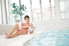 Swimmingpool - Frau entspannen sich mit Buch lizenzfreie stockfotografie