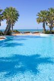 Swimmingpool im spanischen Hotel mit Seeansichten und Palmen Stockbild