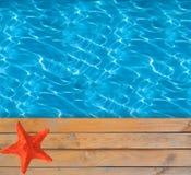 Swimmingpool mit blauem klarem Wasser und hölzerne Plattform mit Sternfischen Stockbilder