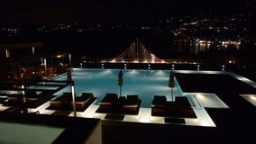 Swimmingpool mit Brunnen in der Nachtbeleuchtung im Luxushotel stock video
