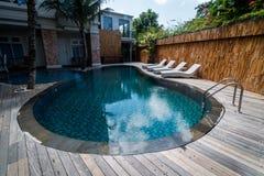 Swimmingpool mit klarem blauem Wasser und Recliners Lizenzfreie Stockfotografie