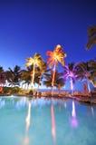 Swimmingpool mit Palmen an der Nachtzeit Lizenzfreies Stockbild