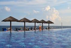 Swimmingpool mit Sunchairs und natürlichen Regenschirmen Stockbild