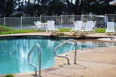 Swimmingpool mit weißen Stühlen Stockfotografie