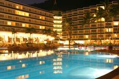 Swimmingpool, Nacht und Palme stockfoto