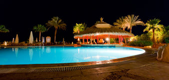 Swimmingpool with a pool bar. A pool bar in a resort, captured in the evening Royalty Free Stock Images