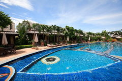 Swimmingpool, Sonnenruhesessel nahe bei dem Garten und Bungalow Stockbild