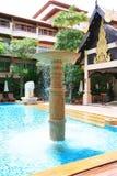 Swimmingpool, Sonnenruhesessel nahe bei dem Garten und Gebäude Stockfoto