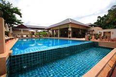 Swimmingpool, Sonnenruhesessel nahe zum Garten und Gebäude Lizenzfreies Stockbild