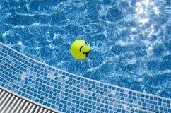 Swimmingpool und Ball mit dem Hervorstehen und dem Blinzeln des Gesichtes Stockfoto
