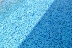 Swimmingpool-Unterseitenätzmittel plätschern und fließen mit Wellenhintergrund Oberfläche des blauen Swimmingpools, Hintergrund d stockfotografie