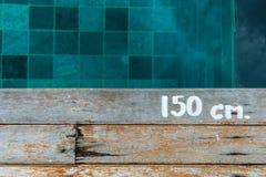 Swimmingpool-Wassertiefenzeichen auf hölzerner Plattform Lizenzfreie Stockfotos