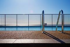 Swimmingpoolrand mit Leiter- und Himmelhintergrund Stockfotos