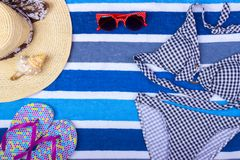 Swimsuit with beach accessories on blue background. Sun Glasses Top View Seashell Shorts Flip flops Swimsuit.  Stock Photos