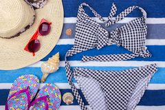 Swimsuit with beach accessories on blue background. Sun Glasses Top View Seashell Shorts Flip flops Swimsuit.  Stock Image