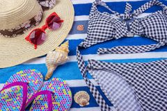 Swimsuit with beach accessories on blue background. Sun Glasses Top View Seashell Shorts Flip flops Swimsuit.  Royalty Free Stock Photos
