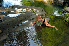 Swimsuit model posing at the nature of mountain river. Elegant young swimsuit model posing at the nature of mountain river Royalty Free Stock Images