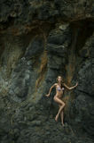 Swimsuit model posing sexy in front of black lava field. On at Palos Verdes, CA Stock Photo