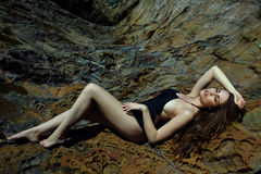 Swimsuit model posing sexy in front of black lava field Royalty Free Stock Image