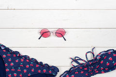 Swimsuit, sunblock and sunglasses on wooden background. Top view Stock Photography