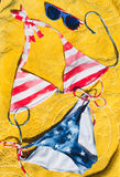 Swimsuit and sunglasses striped american flag placed on yellow cloth Royalty Free Stock Photo