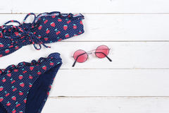 Swimsuit and sunglasses on wooden background. Top view Stock Photo