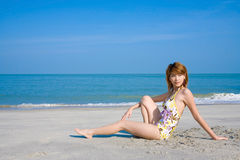 Swimsuit woman by the beach. Woman wearing floral swimsuit sit by the beach looks side way smiling and relaxing Royalty Free Stock Image
