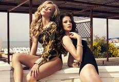 Красивые сексуальные девушки в swimsuites на лете приставают к берегу Стоковая Фотография RF