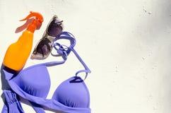 Swimwear, butelka sunscreen, okulary przeciwsłoneczni na białej powierzchni Opr??nia przestrze? dla teksta fotografia stock