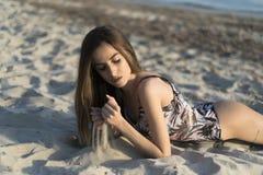 Swimwear d'uso della donna esile, trovantesi sulla sabbia fotografia stock libera da diritti