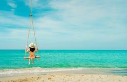 Swimwear di usura di donna ed oscillazione asiatici del cappello le oscillazioni alla spiaggia di sabbia ed a sembrare il bello m fotografia stock