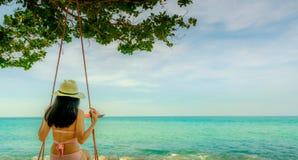 Swimwear di usura di donna ed oscillazione asiatici del cappello le oscillazioni alla spiaggia di sabbia ed a sembrare il bello m fotografia stock libera da diritti