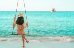 Swimwear di usura di donna ed oscillazione asiatici del cappello le oscillazioni alla spiaggia di sabbia ed a sembrare il bello m immagine stock libera da diritti