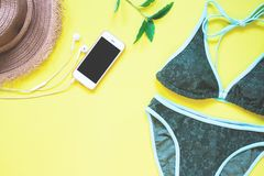 Swimwear in green color with smartphone and earphone flat lay on yellow Royalty Free Stock Image