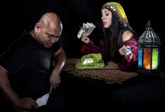 Swindler Fortune Teller. Female fortune teller or con artist swindling money from a male customer via fraud royalty free stock photos