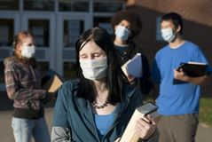 Ebola at school. Students of various ethnic backgrounds wearing masks in front of a school. Focus on teen girl in front Royalty Free Stock Photos