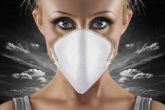 Swine flu woman. Protective face mask on scared blue eyes woman on dark sky background Royalty Free Stock Images