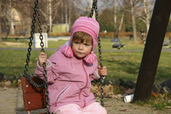 On a swing. Child in a pink cap with pompoms on a swing Royalty Free Stock Image